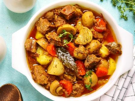 Яхния от задушен свински джолан със зеленчуци - картофи, моркови, лук, гъби и грах в тенджера под налягане - снимка на рецептата